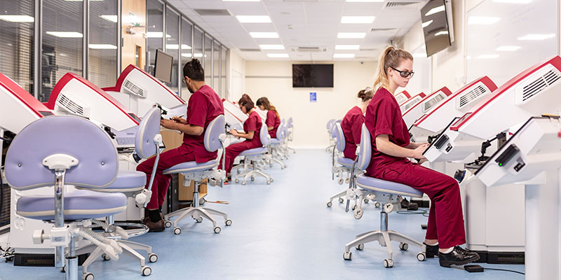 Two students using facilities in the clinical suite in the School of Dentistry