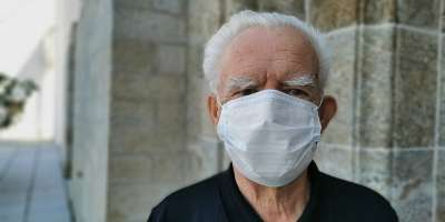 Image of elderly man wearing a white face covering.