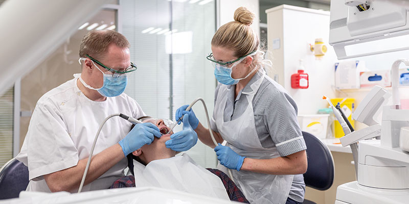 Dental professionals working in clinical suite